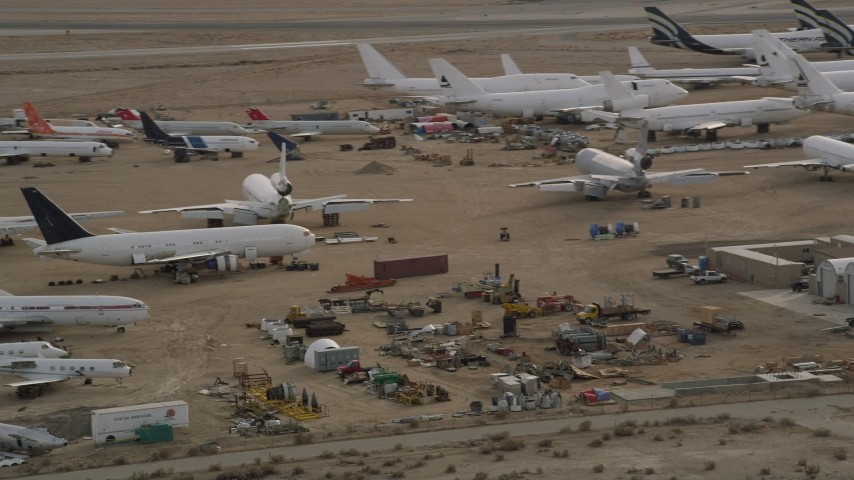 5K stock footage aerial video orbit aircraft and components at a desert boneyard in California, Mojave Air and Space Port Aerial Stock Footage | AX0006_075