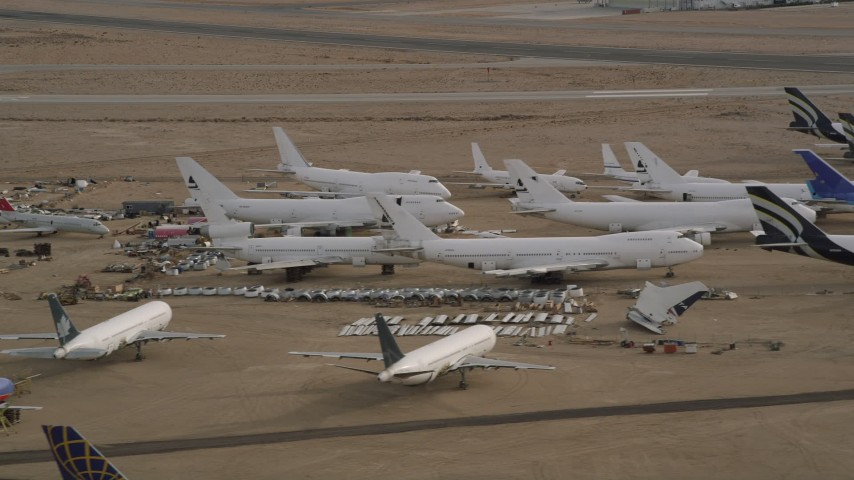 5K stock footage aerial video of jet airplanes and components at an aircraft boneyard in the desert, Mojave Air and Space Port, California Aerial Stock Footage | AX0006_076