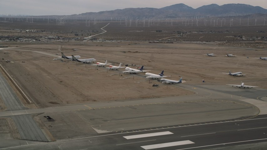 5K aerial video orbit large jet aircraft in a row at a desert boneyard, Mojave Air and Space Port, California Aerial Stock Footage | AX0006_078