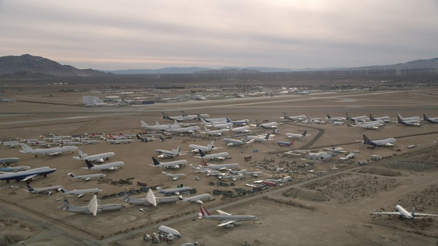 5K stock footage aerial video circle over planes at an aircraft boneyard in the Mojave Desert, California Aerial Stock Footage | AX0006_082E