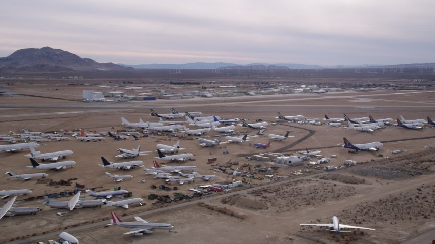 5K stock footage aerial video of an aircraft boneyard and small airport in the Mojave Desert, California Aerial Stock Footage | AX0006_084