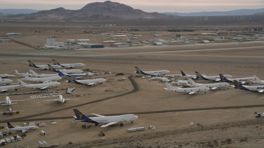 5K aerial video orbit several aircraft at a boneyard by a small airport in the desert, Mojave Air and Space Port, California Aerial Stock Footage | AX0006_085
