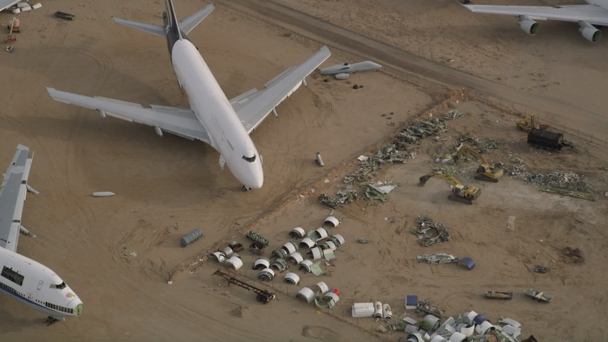 5K stock footage aerial video tilt to bird's eye of jet airplane and components at a desert boneyard, Mojave Air and Space Port, California Aerial Stock Footage | AX0006_089