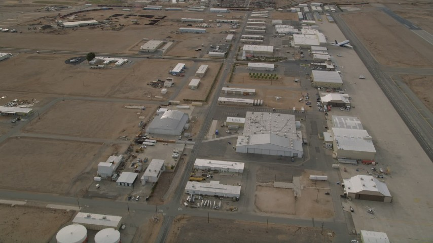 5K stock footage aerial video orbit hangars and runways at the Mojave Air and Space Port in California Aerial Stock Footage AX0006_091 | Axiom Images
