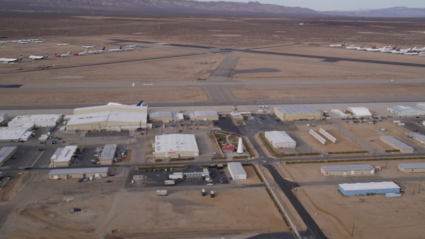 5K aerial video orbit a row of hangars and runways at Mojave Air and Space Port, California Aerial Stock Footage | AX0006_093