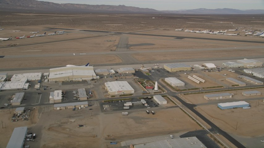 5K stock footage aerial video orbit a row of hangars and runways at Mojave Air and Space Port, California Aerial Stock Footage | AX0006_093E