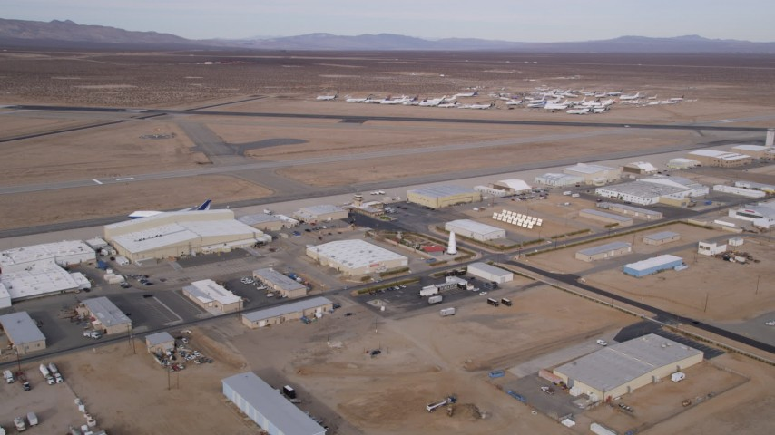 5K stock footage aerial video orbit of runways and a row of hangars at a small airport in California's Mojave Desert Aerial Stock Footage | AX0006_094