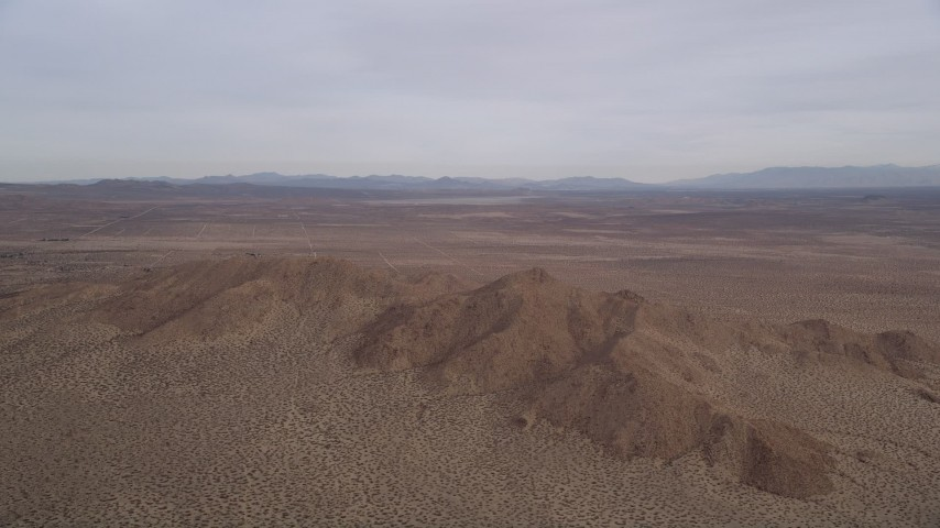 5K stock footage aerial video of panning across open desert to reveal and approach mountains, Mojave Desert, California Aerial Stock Footage | AX0006_115