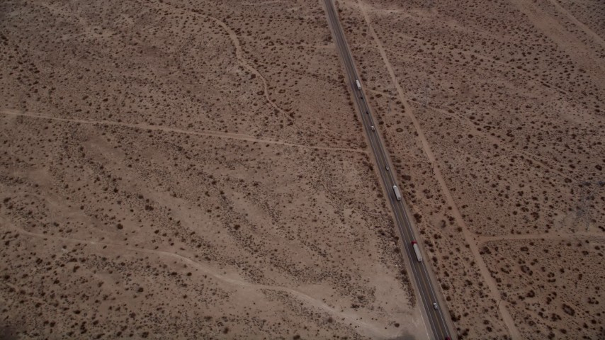 5K stock footage aerial video tilt to bird's eye view of big rigs and cars on Highway 395 through Mojave Desert, California Aerial Stock Footage   AX0006_153