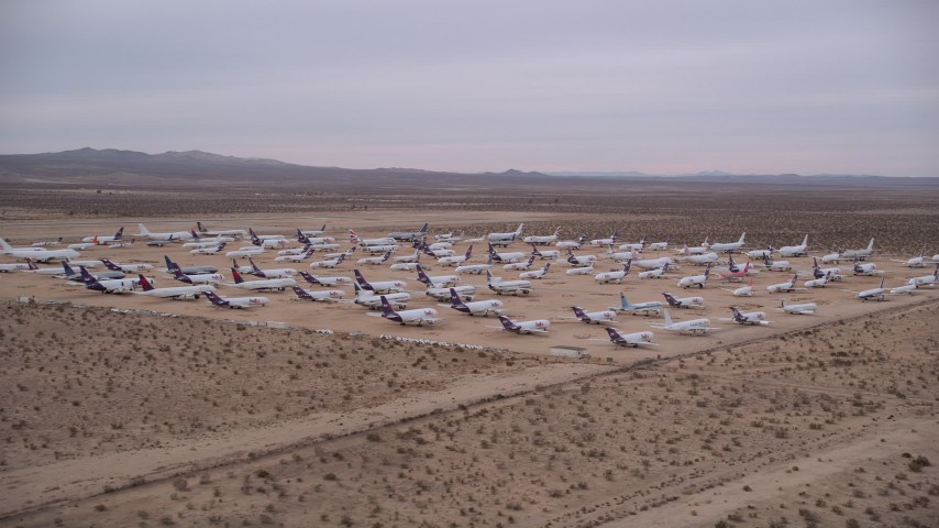 5K aerial video orbit large group of cargo planes at an aircraft boneyard at Victorville Airport at Sunset, California Aerial Stock Footage | AX0007_006