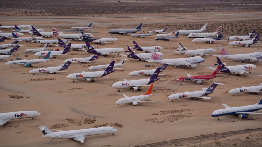 5K aerial video orbit rows of FedEx cargo planes at a desert boneyard at Victorville Airport, California at Sunset Aerial Stock Footage AX0007_007