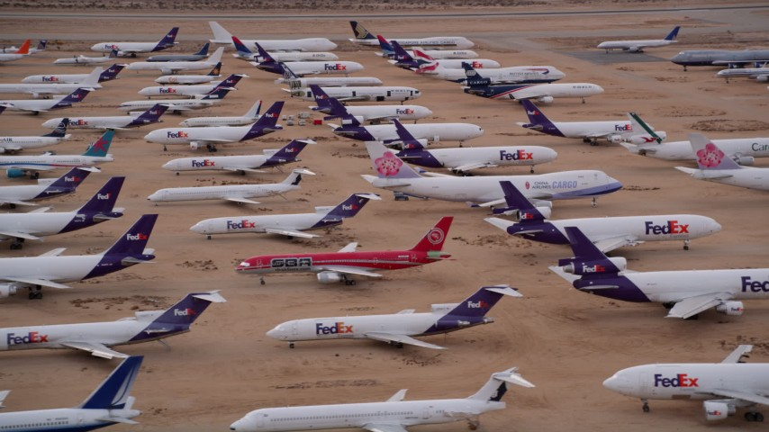 5K aerial video orbiting FedEx cargo planes at an aircraft boneyard in the desert at Sunset, Victorville Airport, California Aerial Stock Footage AX0007_008
