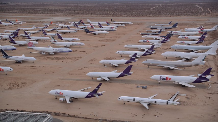 5K aerial video orbit several rows of cargo planes in an aircraft boneyard at Sunset, Victorville Airport, California Aerial Stock Footage | AX0007_009