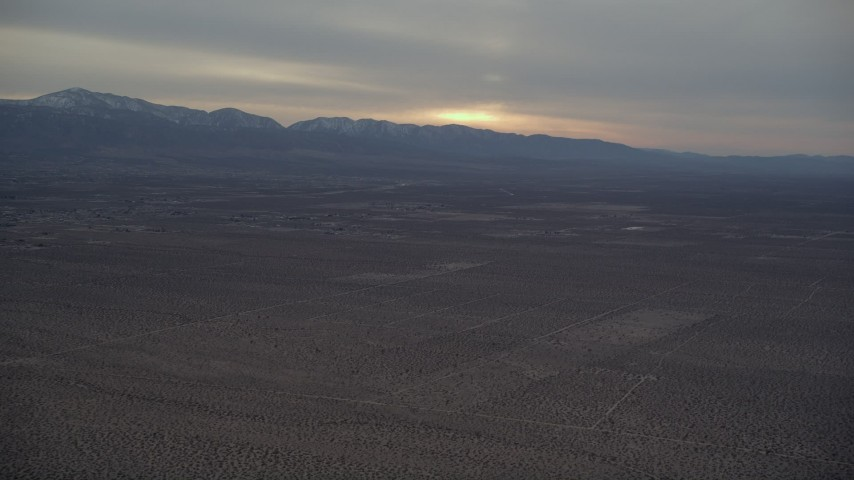 5K stock footage aerial video pan across the Mojave Desert to distant mountains at Sunset, California Aerial Stock Footage | AX0007_019