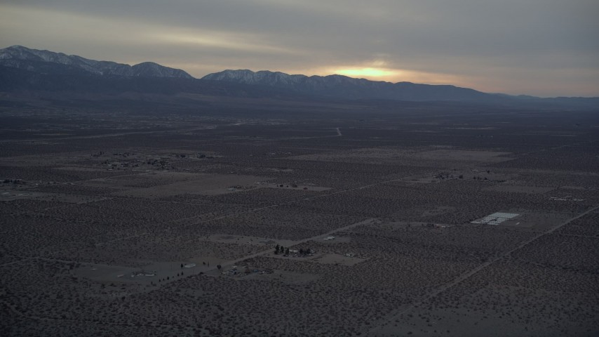 5K stock footage aerial video of rural desert community near mountains with light snow at Sunset, California Aerial Stock Footage | AX0007_023