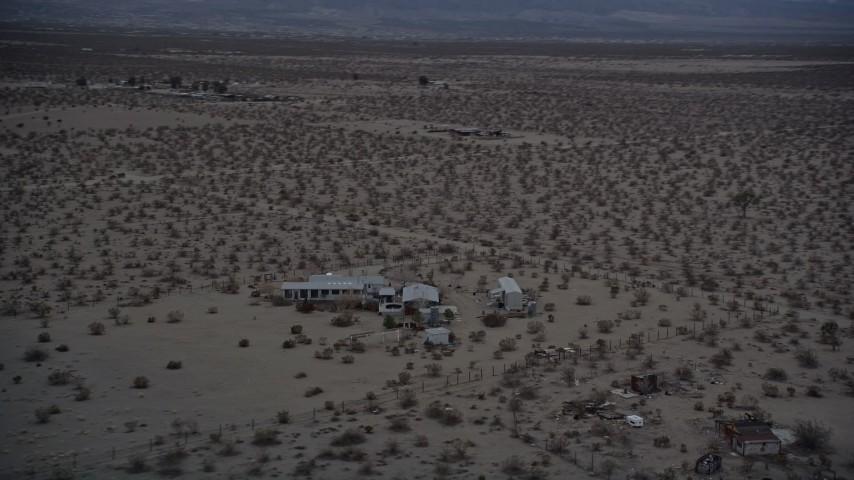 5K aerial video orbiting small desert home in Mojave Desert, California at twilight Aerial Stock Footage   AX0007_025
