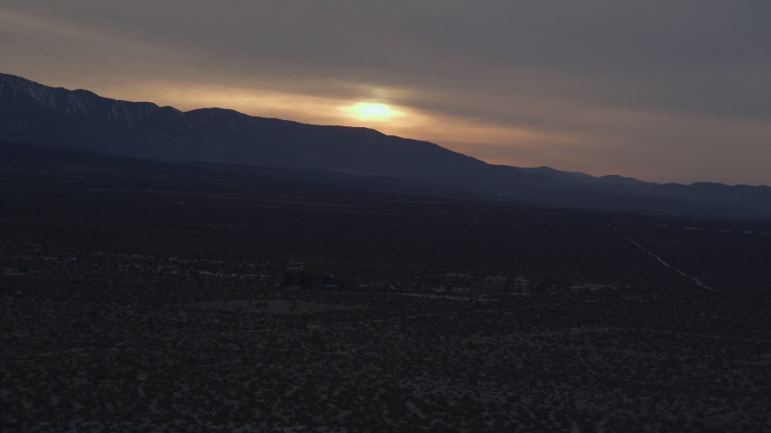 5K stock footage aerial video of sun-lit clouds over distant mountains seen from the Mojave Desert at twilight, California Aerial Stock Footage | AX0007_031