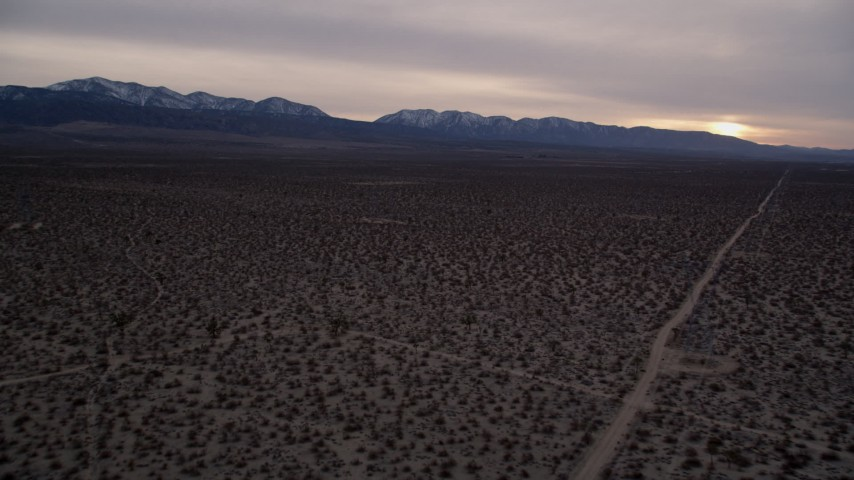 5K stock footage aerial video fly over the Mojave Desert and approach mountains with snow at twilight, California Aerial Stock Footage | AX0007_034