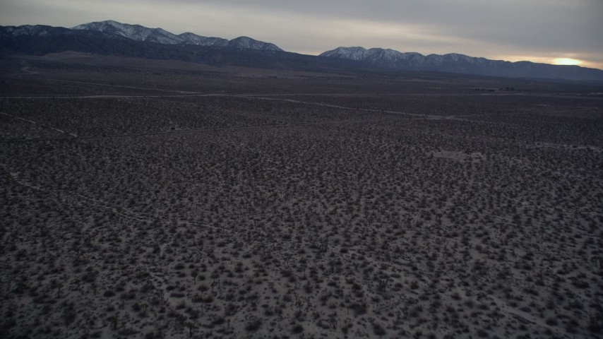 5K stock footage aerial video tilt from desert to reveal mountains with light snow at twilight, Mojave Desert, California Aerial Stock Footage | AX0007_035