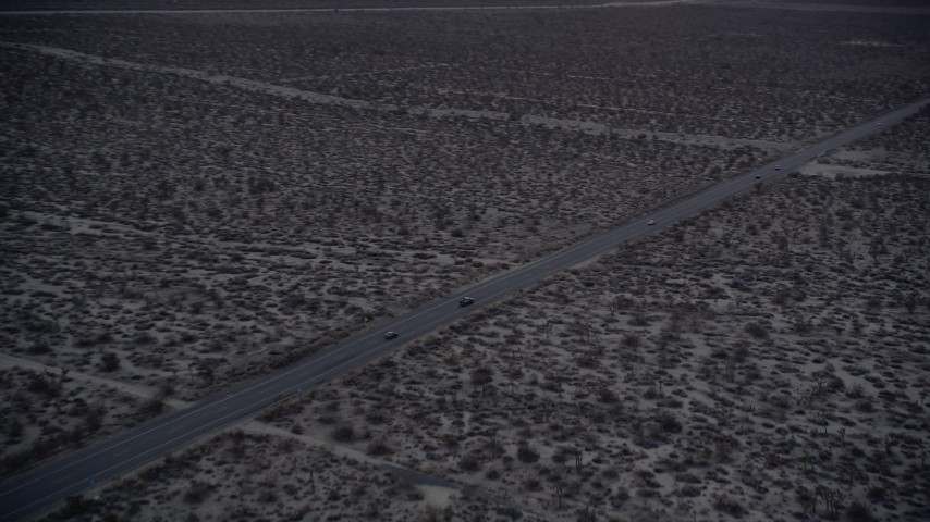 5K stock footage aerial video orbit two cars on desert highway in Mojave Desert at twilight, California Aerial Stock Footage | AX0007_036