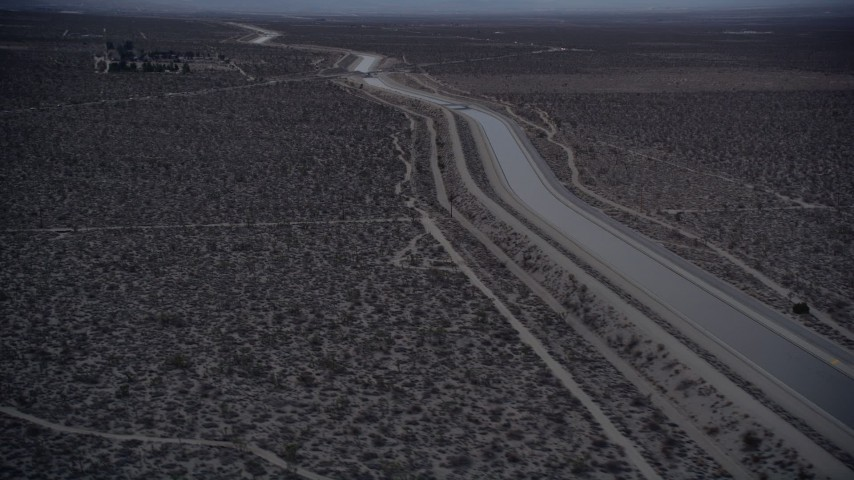 5K aerial  video orbit an aqueduct through the Mojave Desert at twilight, California Aerial Stock Footage | AX0007_037