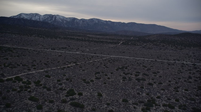 5K stock footage aerial video fly over desert roads in Mojave Desert at twilight, California Aerial Stock Footage | AX0007_042