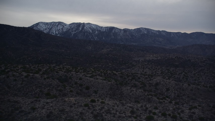 5K stock footage aerial video fly over desert to approach mountains with light snow at twilight in Mojave Desert, California Aerial Stock Footage | AX0007_046