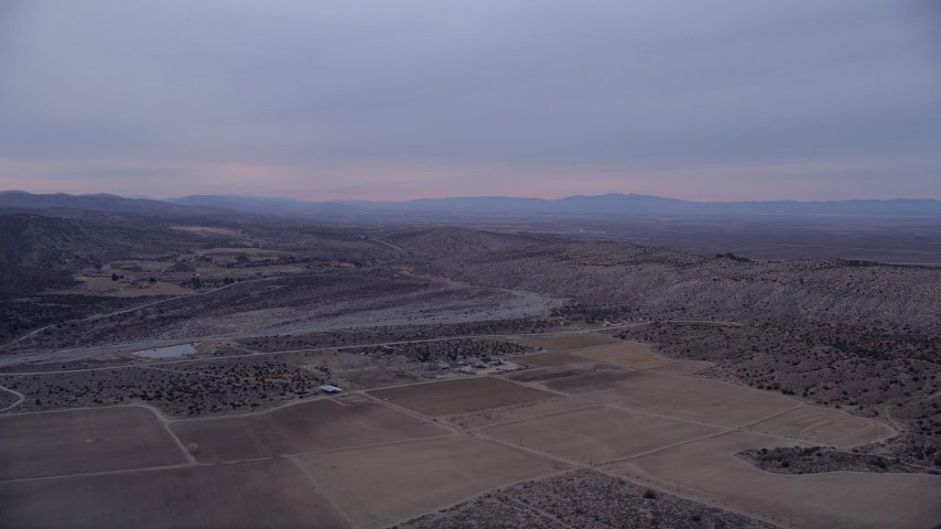 5K stock footage aerial video approach a dry riverbed at twilight in the Mojave Desert, California Aerial Stock Footage | AX0008_002
