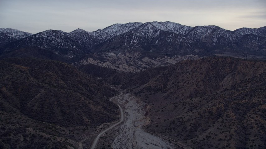 5K stock footage aerial video fly over a dry riverbed toward rock formations and snowy mountains at twilight, San Gabriel Mountains, California Aerial Stock Footage | AX0008_003