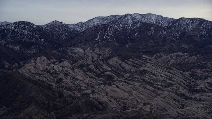5K stock footage aerial video tilt from dry riverbed to reveal rock formations and snowy San Gabriel Mountains at twilight, California Aerial Stock Footage | AX0008_004