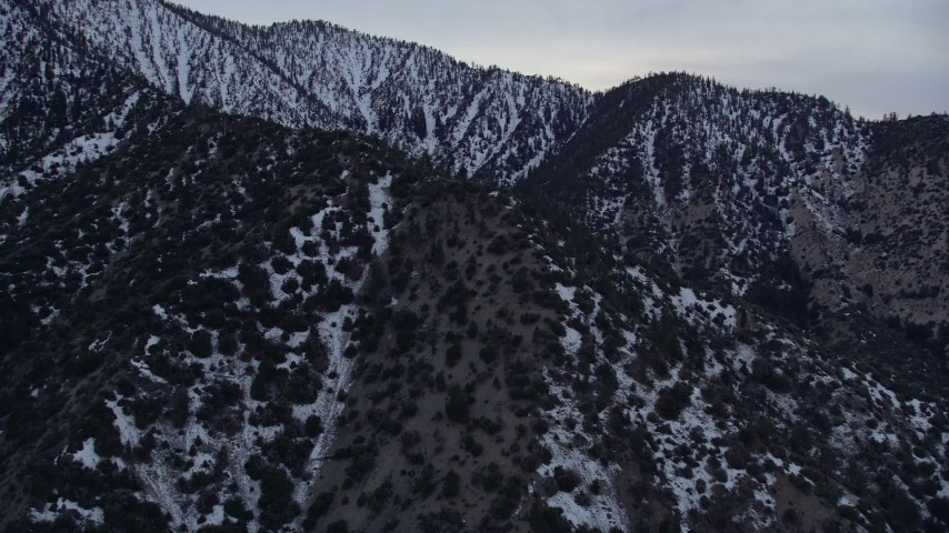 5K stock footage aerial video flyby snowy ridges in the San Gabriel Mountains at twilight in winter, California Aerial Stock Footage | AX0008_008
