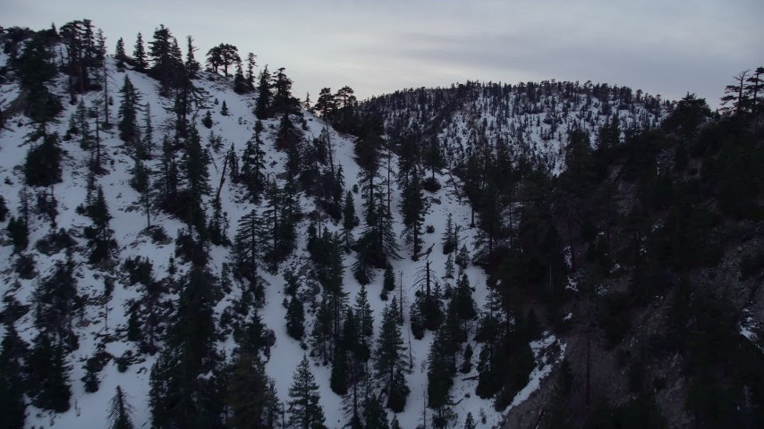 5K stock footage aerial video approach and fly over snowy ridge in the San Gabriel Mountains at twilight, California Aerial Stock Footage | AX0008_011