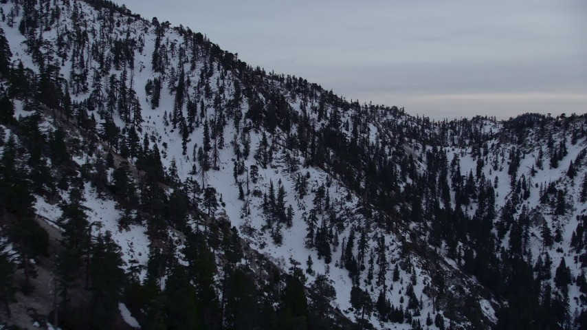 5K aerial video orbit snowy slopes of a peak in the San Gabriel Mountains at twilight in wintertime, California Aerial Stock Footage | AX0008_012