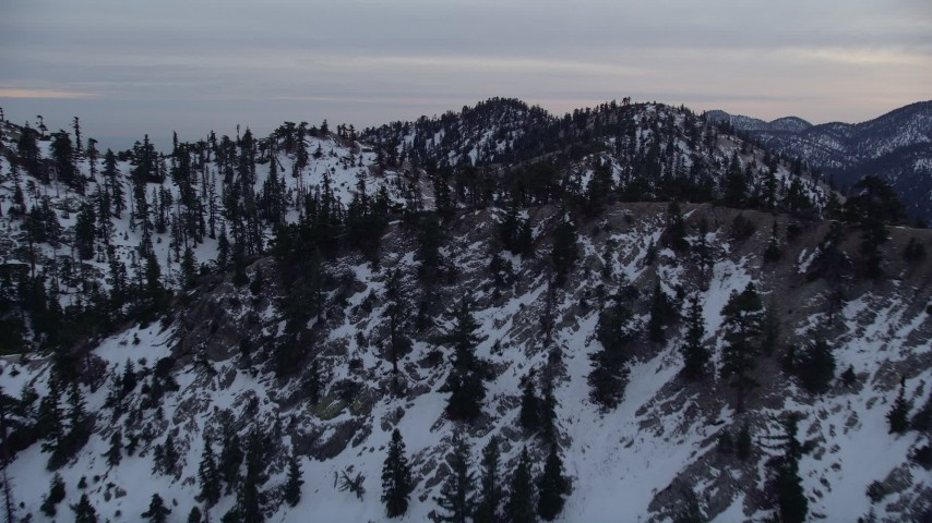 5K stock footage aerial video approach and fly over ridges with winter snow in the San Gabriel Mountains, California, twilight Aerial Stock Footage | AX0008_013