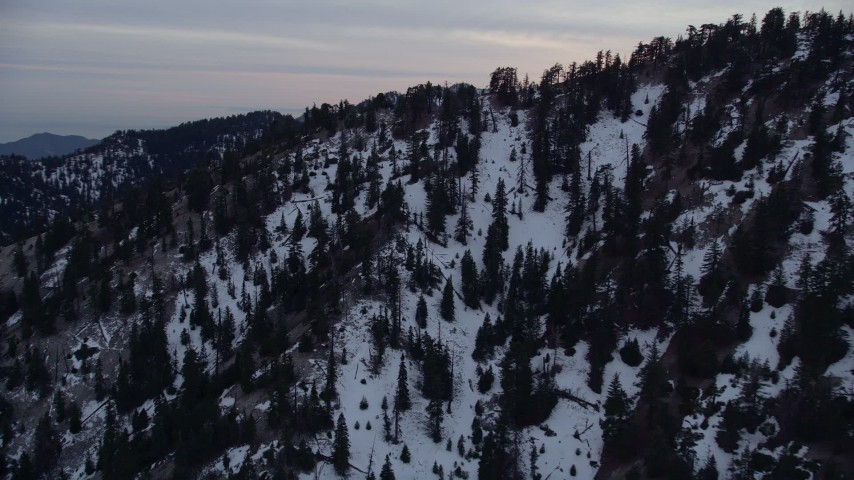 5K aerial video orbit slopes with winter snow in the San Gabriel Mountains at twilight, California Aerial Stock Footage | AX0008_015