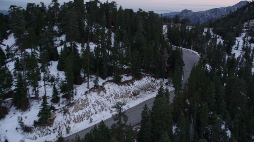 5K stock footage aerial video fly over lonely mountain road with winter snow through San Gabriel Mountains at twilight, California Aerial Stock Footage | AX0008_018