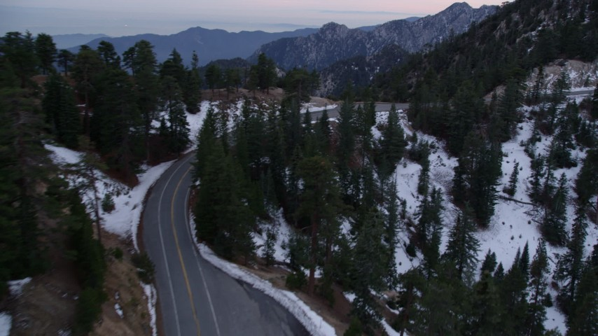 5K stock footage aerial video pan across lonely road with winter snow in the San Gabriel Mountains at twilight, California Aerial Stock Footage | AX0008_019
