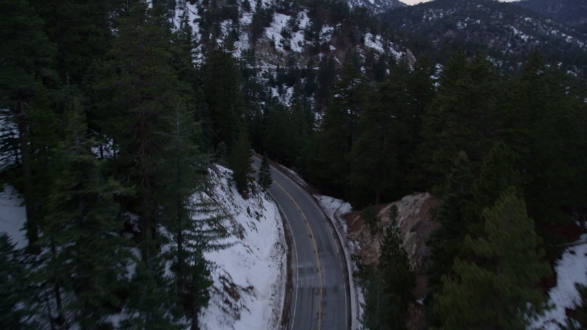 5K stock footage aerial video of following road with winter snow through San Gabriel Mountains at twilight, California Aerial Stock Footage | AX0008_020