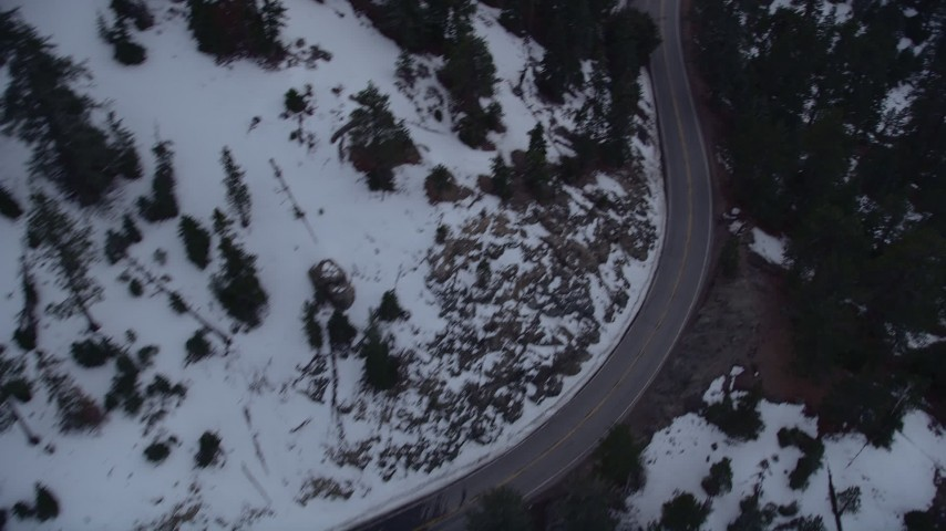 5K stock footage aerial video bird's eye of mountain road with winter snow through San Gabriel Mountains at twilight, California Aerial Stock Footage | AX0008_027