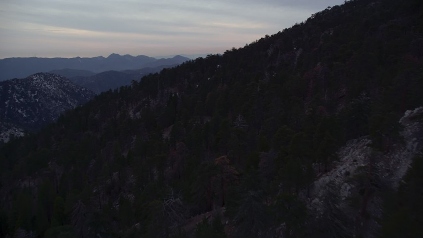 5K stock footage aerial video of dense forest on snowy slopes in the San Gabriel Mountains at twilight, California Aerial Stock Footage | AX0008_033