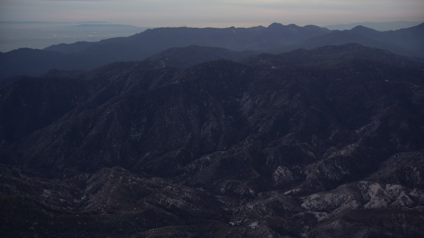 5K stock footage aerial video tilt up and approach San Gabriel Mountains at twilight, California Aerial Stock Footage | AX0008_036