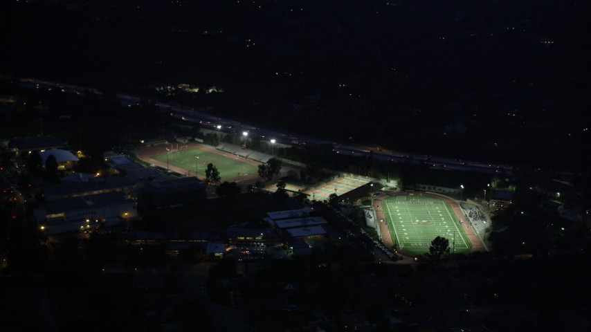 5K stock footage aerial video approach football and track fields at night in La Cañada Flintridge, California Aerial Stock Footage | AX0008_067