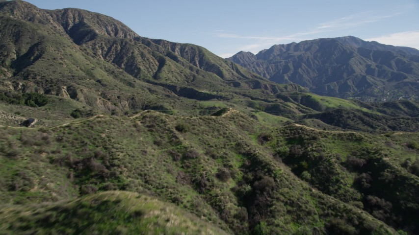 5K aerial video fly over a dirt road in the San Gabriel Mountains and tilt to reveal tall peaks, California Aerial Stock Footage | AX0009_004