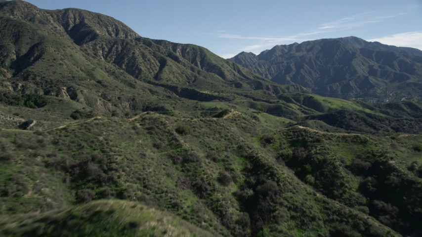 5K stock footage aerial video fly over a dirt road in the San Gabriel Mountains and tilt to reveal tall peaks, California Aerial Stock Footage | AX0009_004E