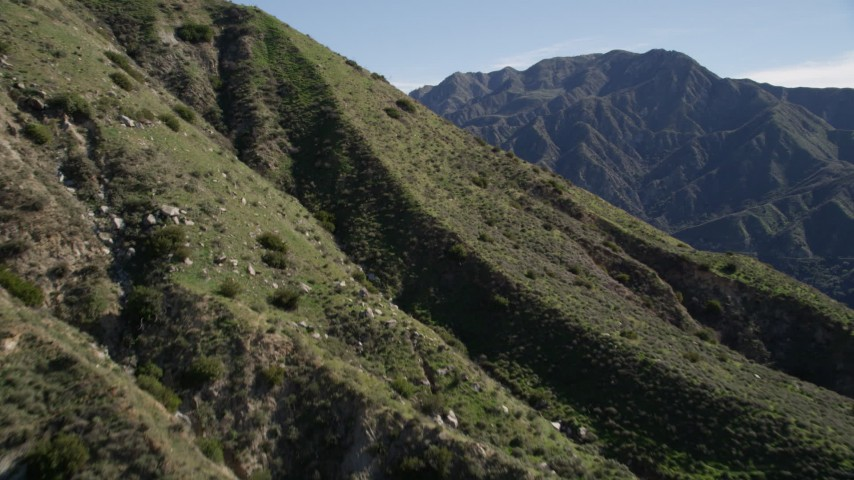 5K aerial video fly over a slope and reveal green ridges in the San Gabriel Mountains, California Aerial Stock Footage | AX0009_007