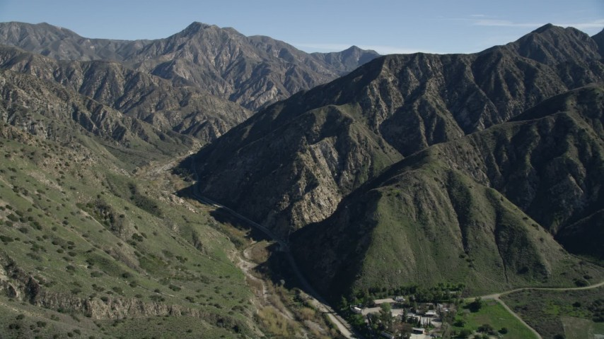 5K stock footage aerial video approach road at the base of green ridges in the San Gabriel Mountains, California Aerial Stock Footage | AX0009_008