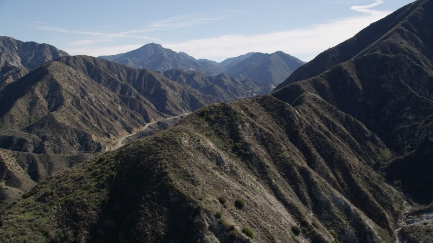 5K stock footage aerial video fly over ridge to reveal road in the San Gabriel Mountains, California Aerial Stock Footage | AX0009_012
