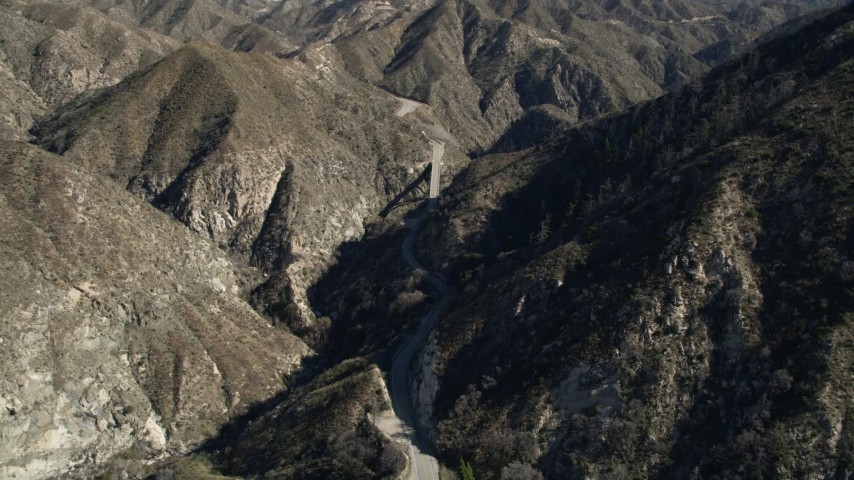 5K aerial video fly over a mountain to reveal road and small bridge in the San Gabriel Mountains, California Aerial Stock Footage | AX0009_022