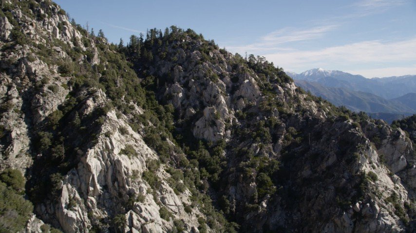 5K stock footage aerial video approach and fly over rocky slopes with trees in the San Gabriel Mountains, California Aerial Stock Footage | AX0009_034