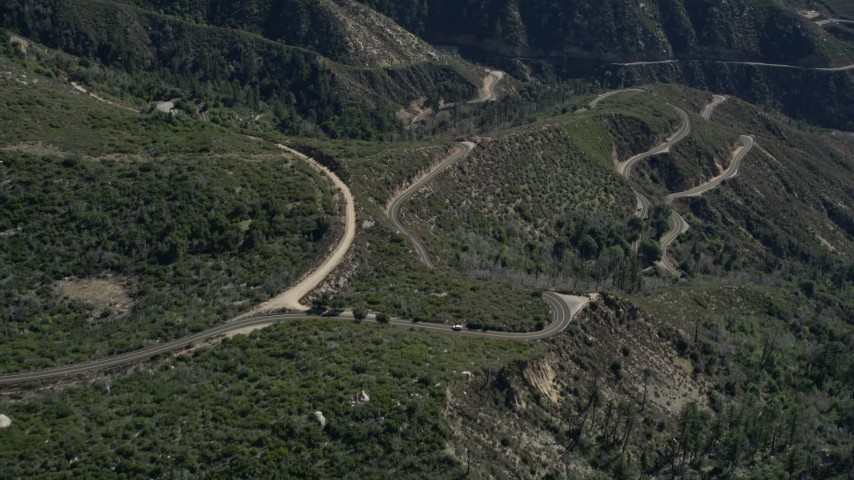 5K stock footage aerial video approach and tilt to curved roads in the San Gabriel Mountains, California Aerial Stock Footage | AX0009_040
